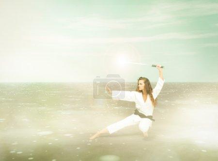 Girl with judo uniform ready to hit with katana