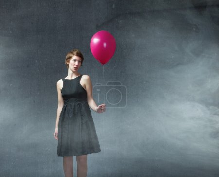 Woman with red balloon on hand