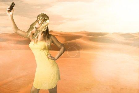 Photo pour Femme au masque de sphinx égyptien prendre un selfie, la lumière dure et ensoleillée - image libre de droit