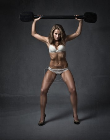 Photo for Girl with weights on shoulder, dark background and whote lingerie - Royalty Free Image