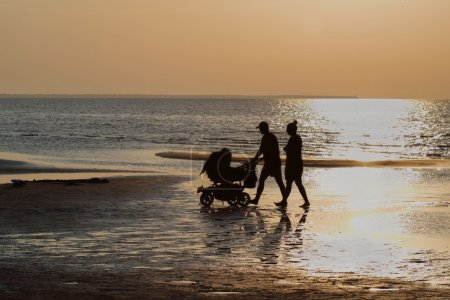 Silhouettes of man and woman with baby carriage wa...