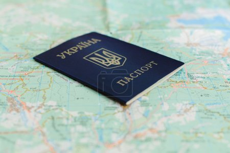 Photo pour Une image d'un passeport ukrainien sur un arrière-plan de la carte touristique - image libre de droit
