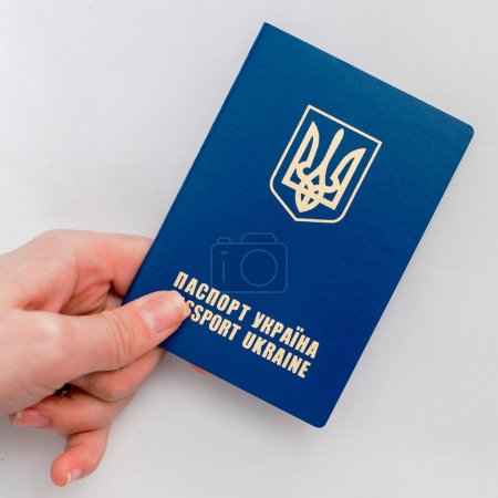 Ukrainian passport in hand on a white background