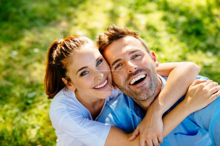 Photo for Happy couple hugging while  sitting on grass in park - Royalty Free Image