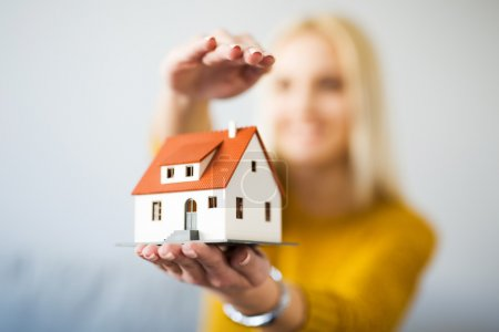 Photo for Home insurance concept - young woman holding home figurine - Royalty Free Image
