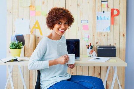 Photo pour Jeune femme heureuse, concepteur assis au bureau avec une tasse de café en regardant la caméra - image libre de droit