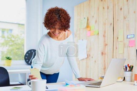 Photo for Attractive female designer working on laptop standing by a desk - Royalty Free Image