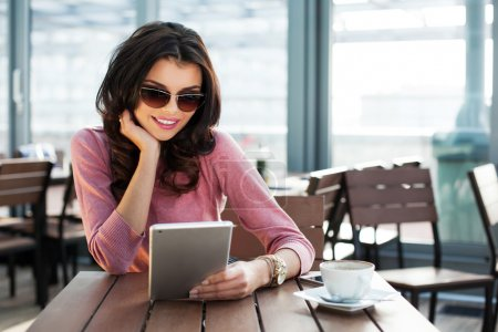 Photo for Young attractive woman surfing on her tablet while sitting in a cafe - Royalty Free Image