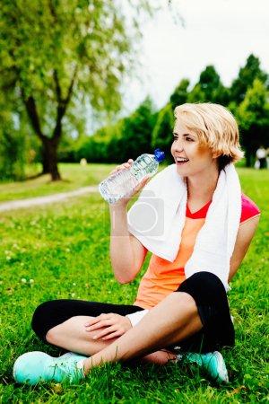 Woman runner drinking water