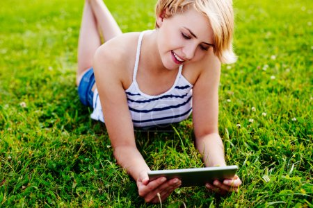 Photo for Portrait of a young woman using a tablet and lying on the grass - Royalty Free Image