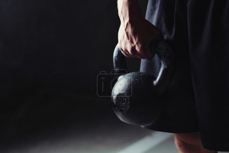 Photo for Close-up of a muscular hand holding a kettlebell - Royalty Free Image