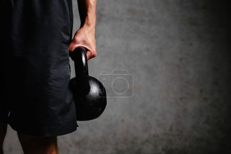 Photo for Photo of a muscular arm holding a kettlebell - Royalty Free Image