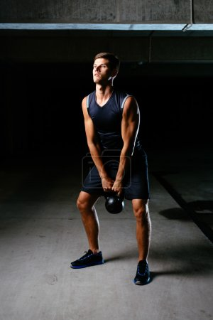 Muscular athlete with a kettlebell