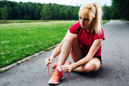 Female jogger lacing up her shoes