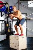Muscular man perfecting the box jump