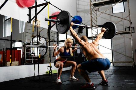 Photo pour Photo d'un couple d'haltérophiles s'entraînant avec des barbells - image libre de droit