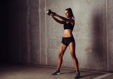 Photo for Brunette sportswoman working out her arms with a kettlebell - Royalty Free Image