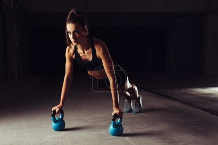 Photo for Slim brunette bodybuilder doing push-ups exercises on kettlebells - Royalty Free Image