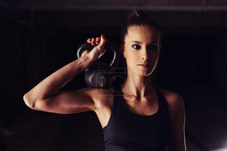 Female bodybuilder toning her arm