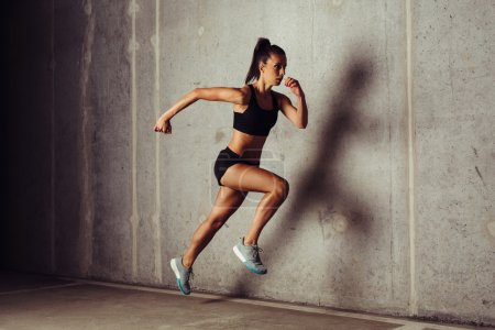Photo for Slim attractive sportswoman running against a concrete background - Royalty Free Image