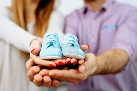 Prengant couple holding baby shoes