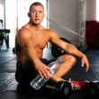 Young muscular man resting after gym workout...