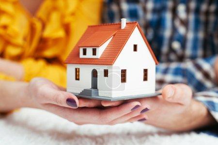 Photo pour Gros plan d'un jeune couple tenant une maison miniature - image libre de droit