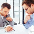 Two architects sitting at a desk and busy with cre...