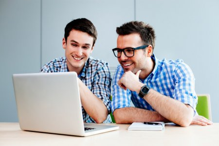 Webdesigners looking at their project on laptop