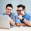 Two smiling webdesigners looking at their project ...