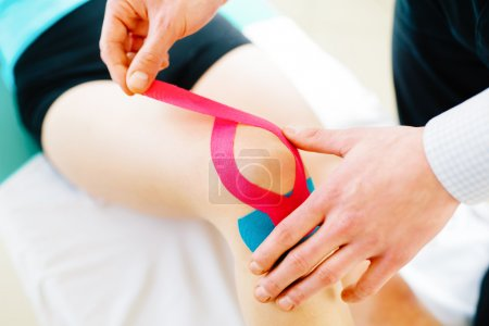 Woman massages injured knee