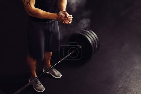 Photo for Athlete clapping hands with talc before deadlift barbell workout - Royalty Free Image