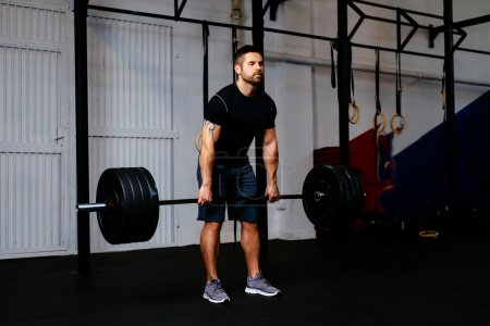Photo for Young man during deadlift exercise with barbell at gym - Royalty Free Image