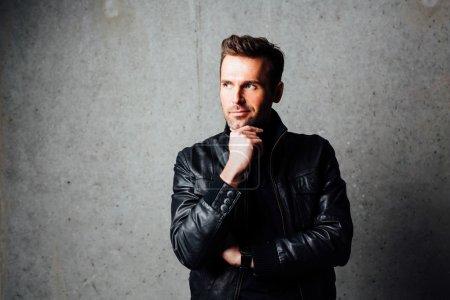 Photo pour Bel homme pensif en blouson de cuir, debout contre le mur en béton et en regardant loin - image libre de droit