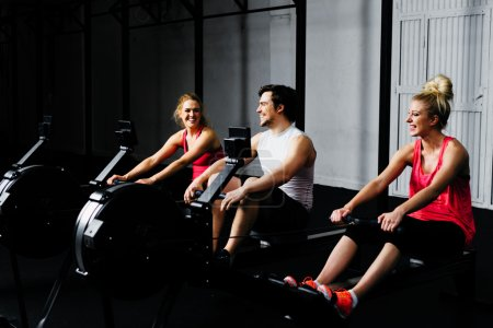 friends training on rowing machine