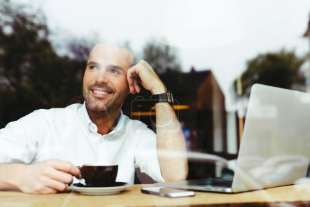 Happy young man drinking coffee at cafe
