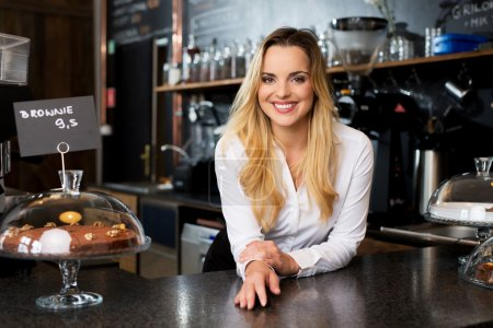 Smiling female cafe owner