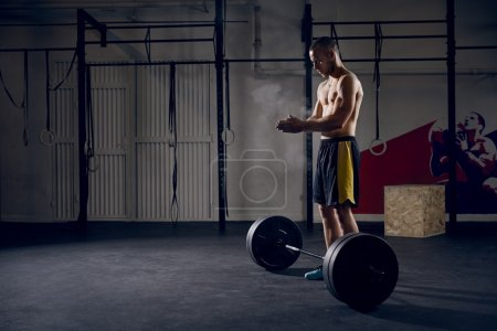 Man at gym clapping hands before lifting barbells
