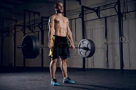 Young athlete lifting barbells