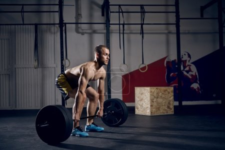 Young shirtless man doing deadlift exercise