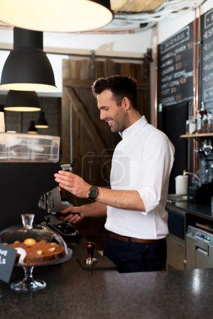 Happy man making coffee