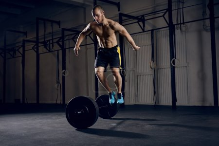 Men jumping over barbells