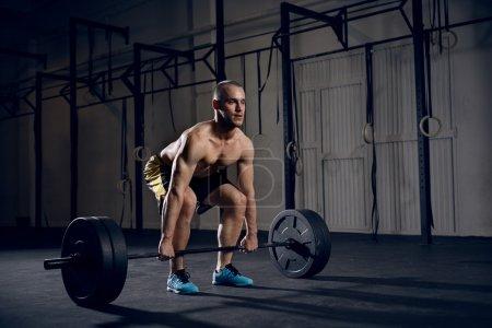 Shirtless man lifting barbells