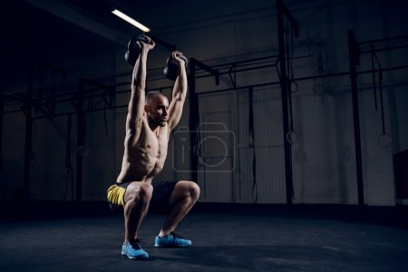 Squat with kettlebells over head