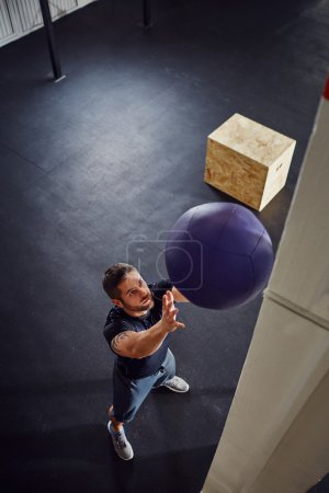 Photo for Yong athlete doing wall ball exercise at gym - Royalty Free Image