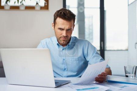 Mid adult man paying bills at home