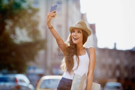 Photo for Happy tourist taking selfie on city street - Royalty Free Image