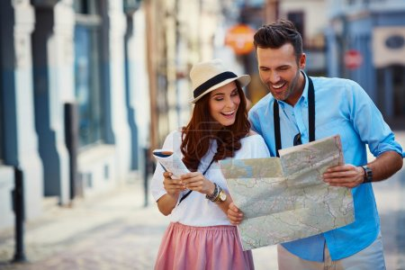 Photo for Young couple traveling, reading map in the city - Royalty Free Image