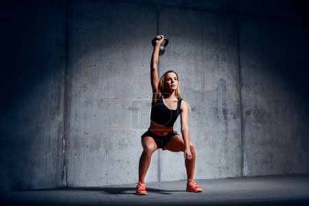 Photo for Woman doing Kettlebell Overhead Exercise - Royalty Free Image