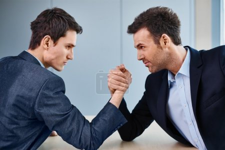 two businessman arm wrestling